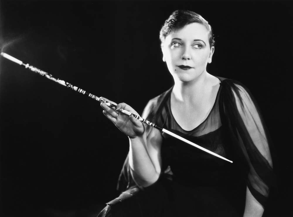 English film and theatre costume designer Dolly Tree (1899 - 1962) posing with a long cigarette holder, London, 7th September 1926. (Photo by Sasha/Hulton Archive/Getty Images)