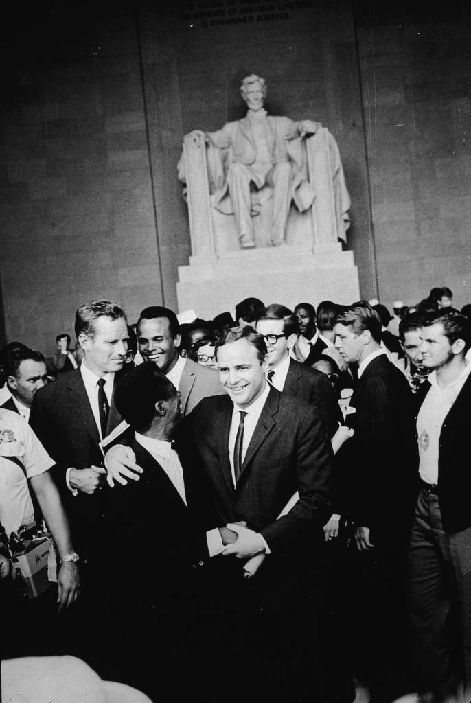 American actor Marlon Brando (1924 - 2004) stands with his arm around poet James Baldwin, surrounded by actors Charlton Heston (L), Harry Belafonte and others gathered at the Lincoln Memorial during the Civil Rights March on Washington, D.C., August 28, 1963. (Photo by Hulton Archive/Getty Images)