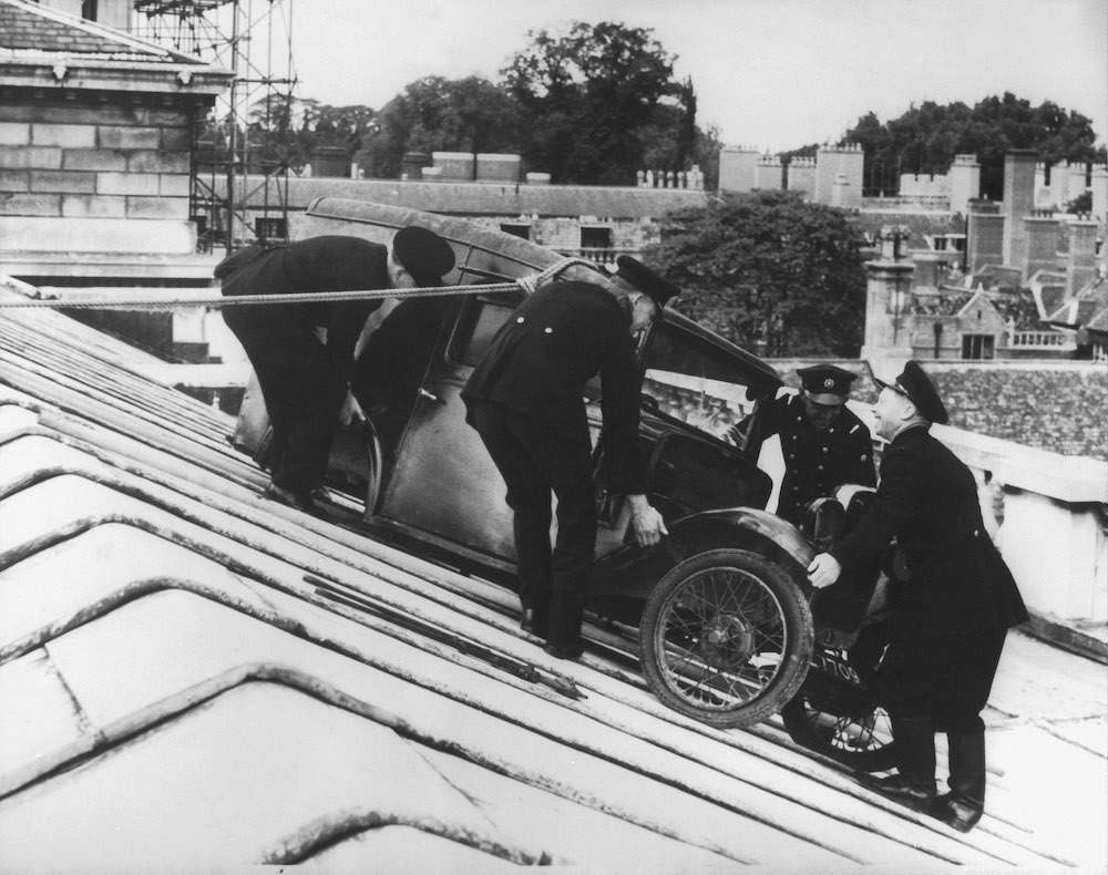 Firemen finally manage to lower an Austin Seven van from the roof of the Cambridge University Senate House, 1958. The van had been hoisted onto the roof as an undergraduate prank on the night of June 7th. (Photo by Central Press/Hulton Archive/Getty Images)