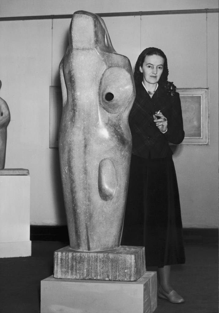 British sculptor Barbara Hepworth (1903 - 1975) posing with a life size stone sculpture at an exhibition of her work, 7th February 1950.  (Photo by Fred Morley/Fox Photos/Getty Images)