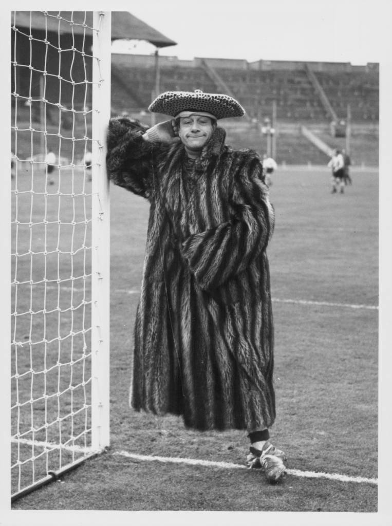 Comedian Jimmy Jewel wearing a fur coat, football boots and a funny hat, joking around as the goalkeeper in a football match between the Wembley Stadium staff and the cast of 'Babes in the Wood', London, January 24th 1956. (Photo by J. Wilds/Keystone/Getty Images)