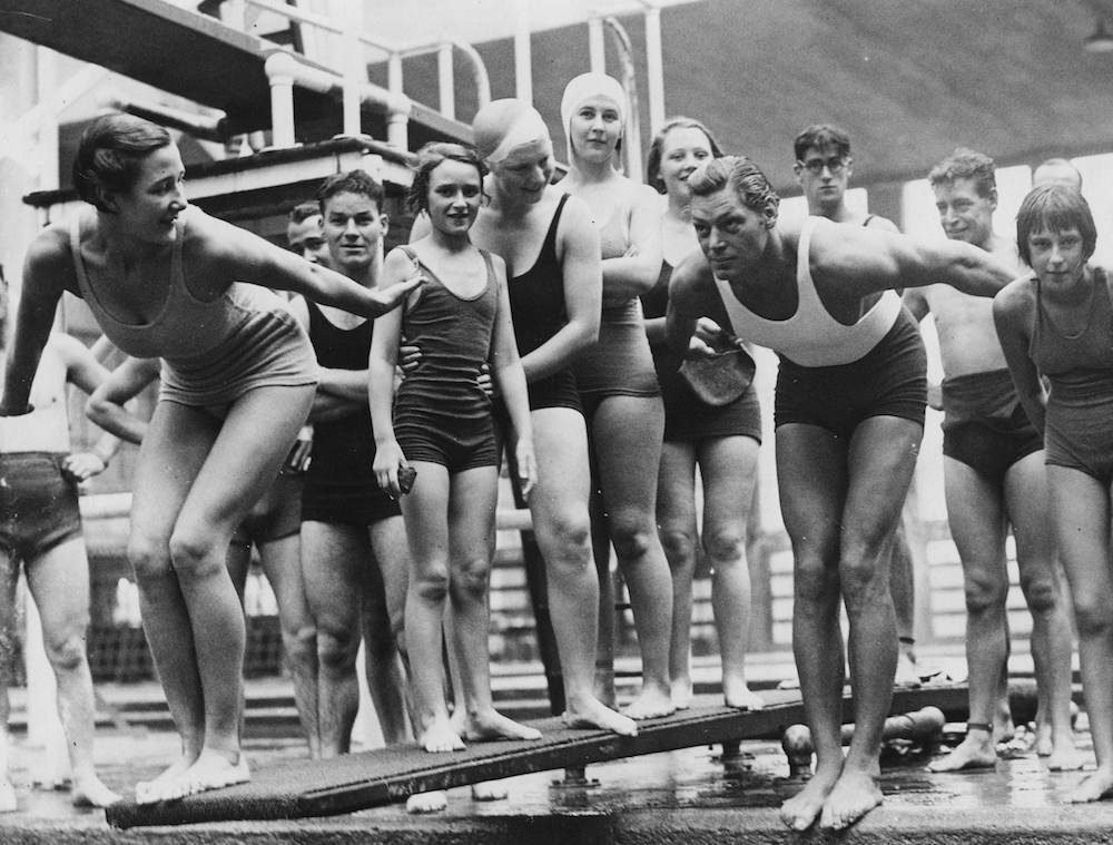 Actor Johnny Weissmuller in a dive position at the start of a swimming race, with a group of bathers at the Empire Pool, Wembley, London, October 7th 1934. (Photo by R. Wesley/Fox Photos/Getty Images)
