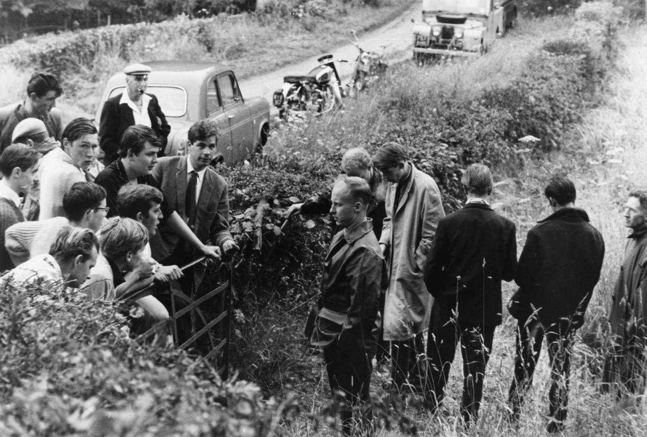 Politician John Tyndall (with his hands in his pockets), Secretary of the British National Socialist Movement, is accosted by protesting villagers at a private campsite rally, Temple Guiting, the Cotswolds, August 7th 1962. (Photo by Keystone/Hulton Archive/Getty Images)