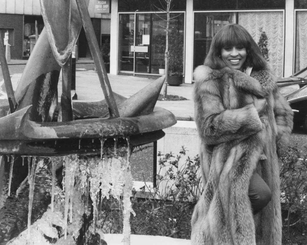 Singer Tina Turner wearing a fur coat as she poses next to a fountain on the eve of her first solo performance in Britain, at the Inn on the Park Hotel in London, February 10th 1978. (Photo by Keystone/Hulton Archive/Getty Images)