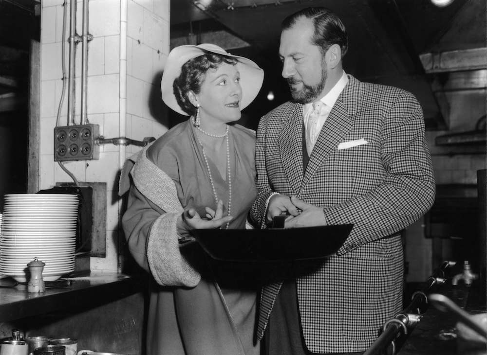 English television cook Fanny Cradock (1909 - 1994) meets French chef Raymond Oliver at the Mirabelle restaurant in London, 7th January 1956. Mrs Cradock is hoping to disprove Mr Oliver's assertion that 'women cannot cook' by demonstrating her skills for him and a panel of experts at the Cafe Royal. (Photo by Keystone/Hulton Archive/Getty Images)