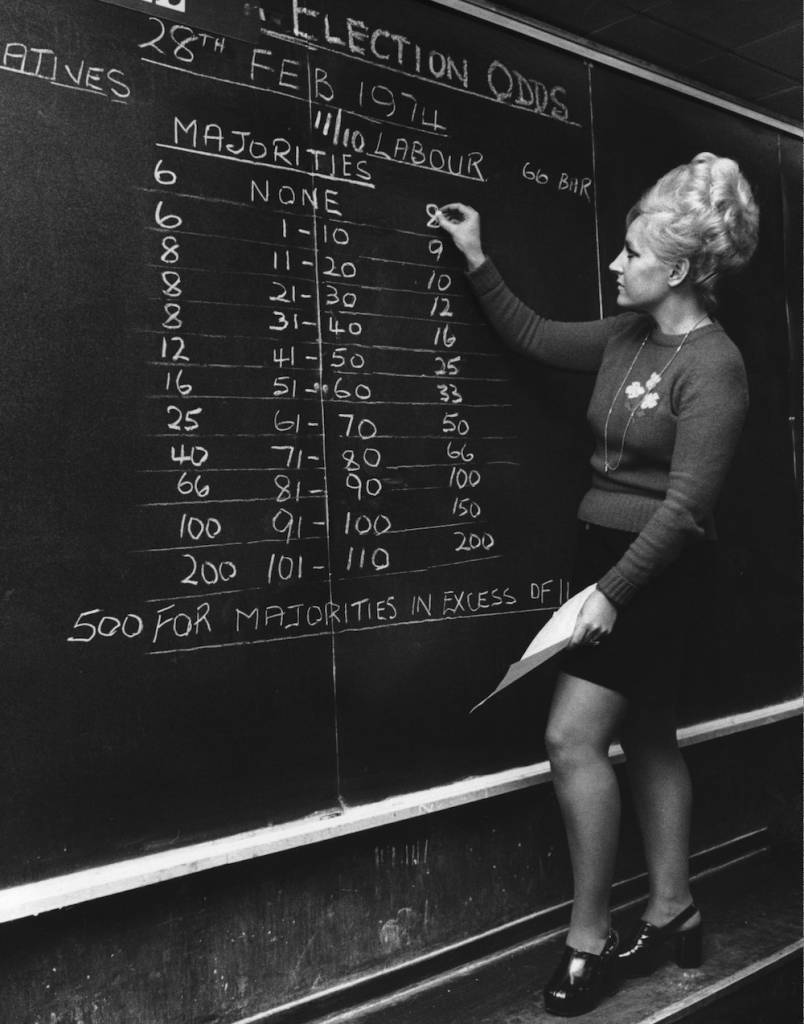 Barbara Elson, of bookmakers William Hill, chalks up the betting odds on majorities in the forthcoming general election, 7th February 1974. The firm made the Conservatives 6-4 favourites to win. The election resulted in a hung parliament with Labour Prime Minister Harold Wilson in power, however. (Photo by Wesley/Keystone/Hulton Archive/Getty Images)