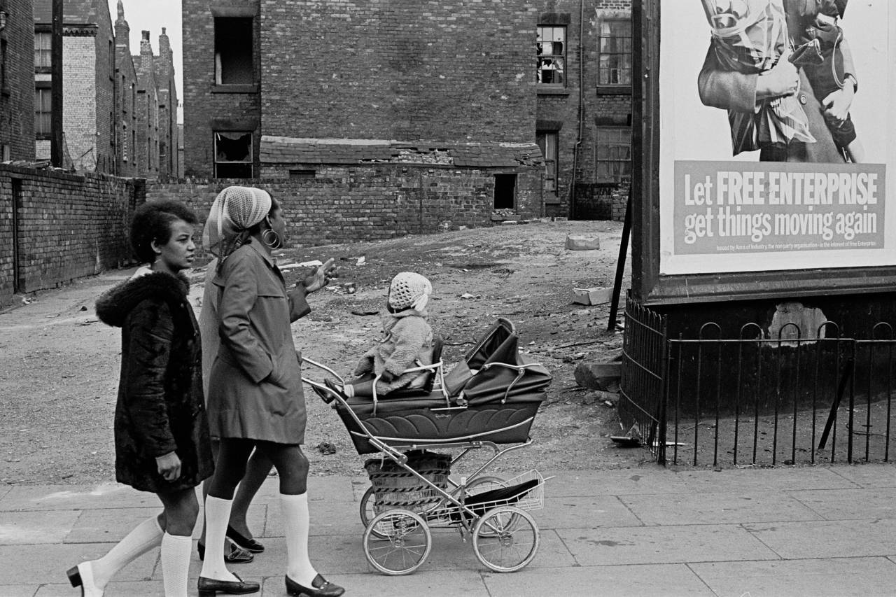 Liverpudlians walking past an election poster 1969 Liverpool 8