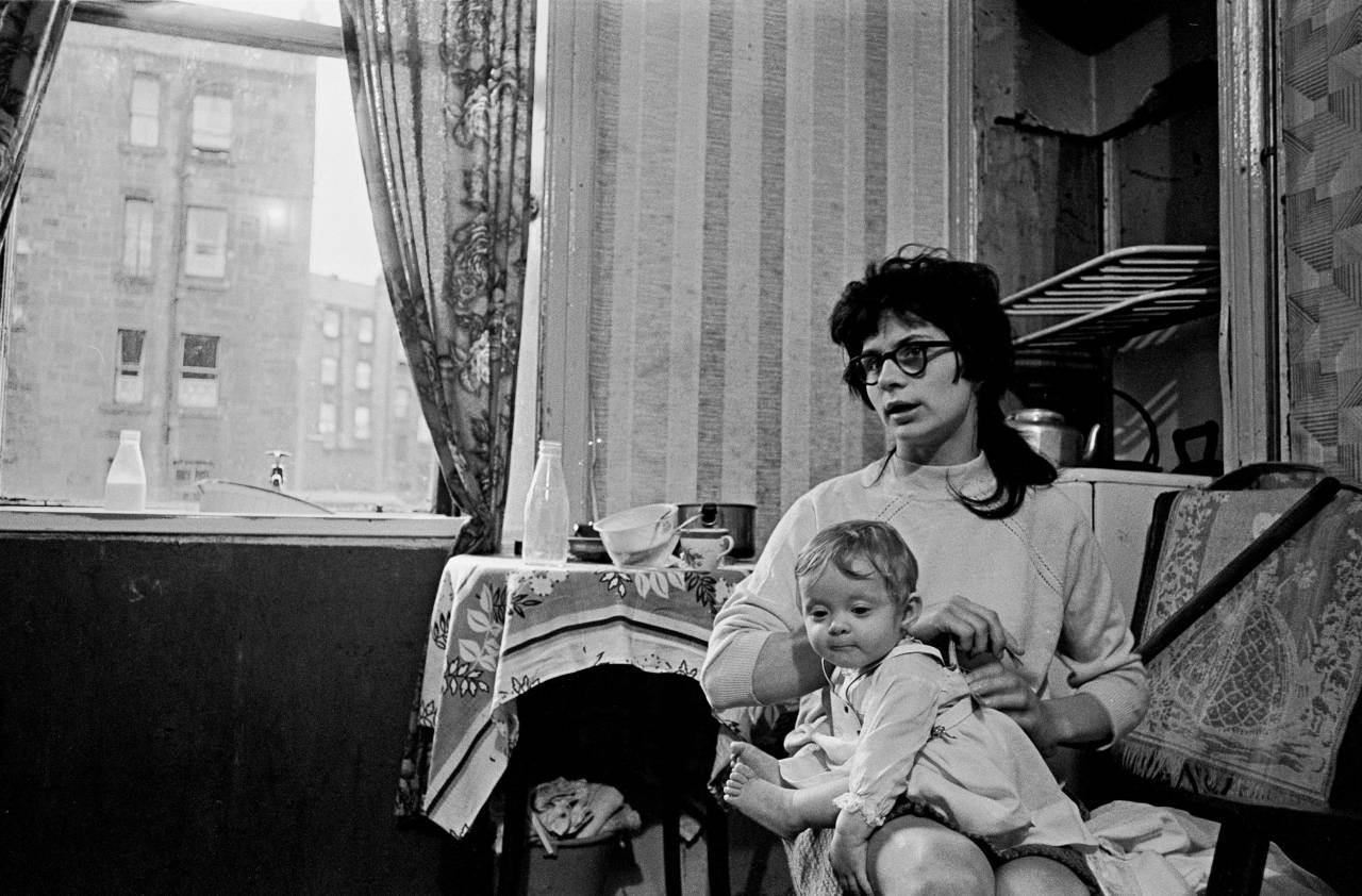 Mother and child living in a damp and semi derelict tenement, Glasgow 1971