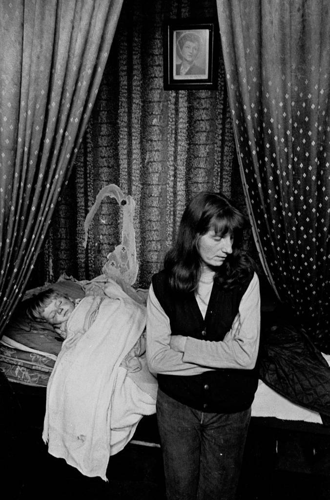 Mother and sleeping child, single end tenement flat, Glasgow Maryhill 1971
