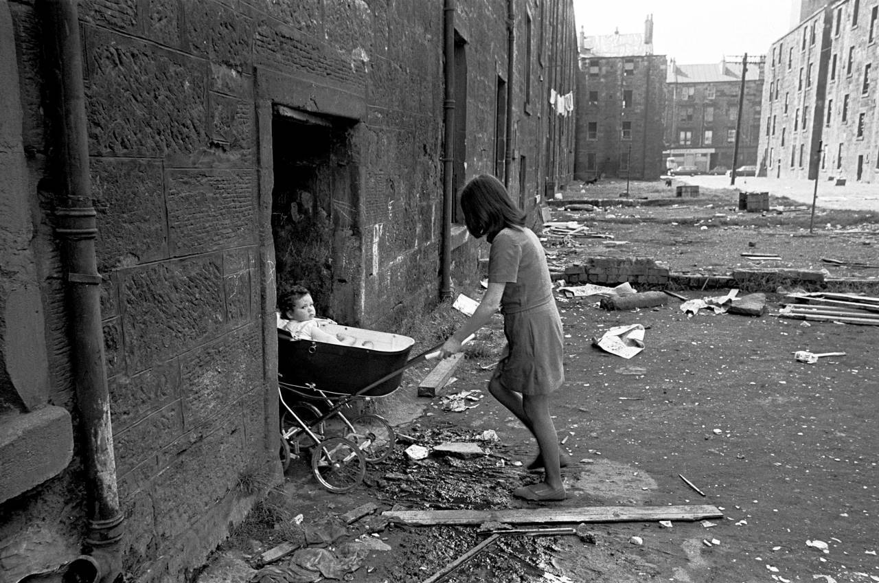 Mother takes her baby inside her condemned tenement block Gorbals 1970