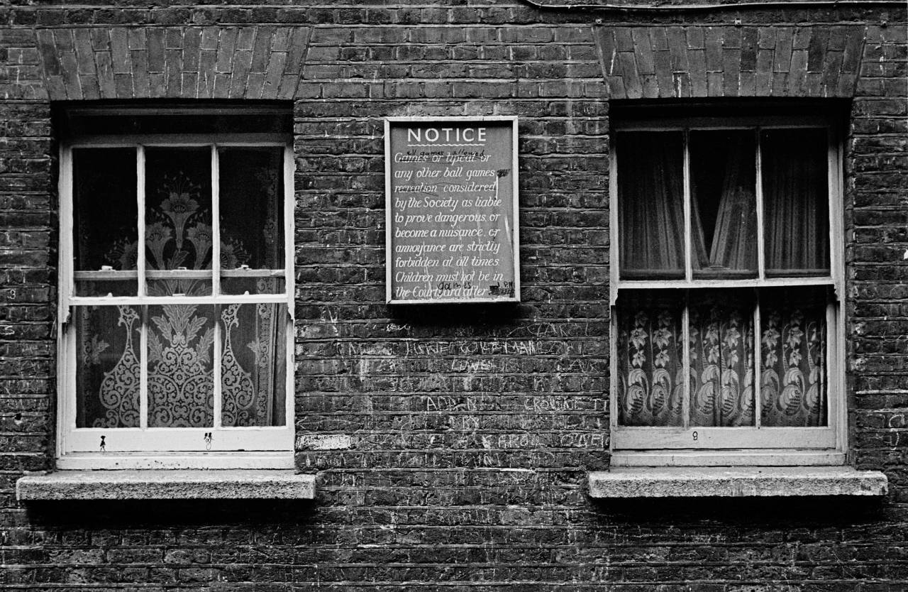 Notice on wall of courtyard, Rothschild dwellings 1969