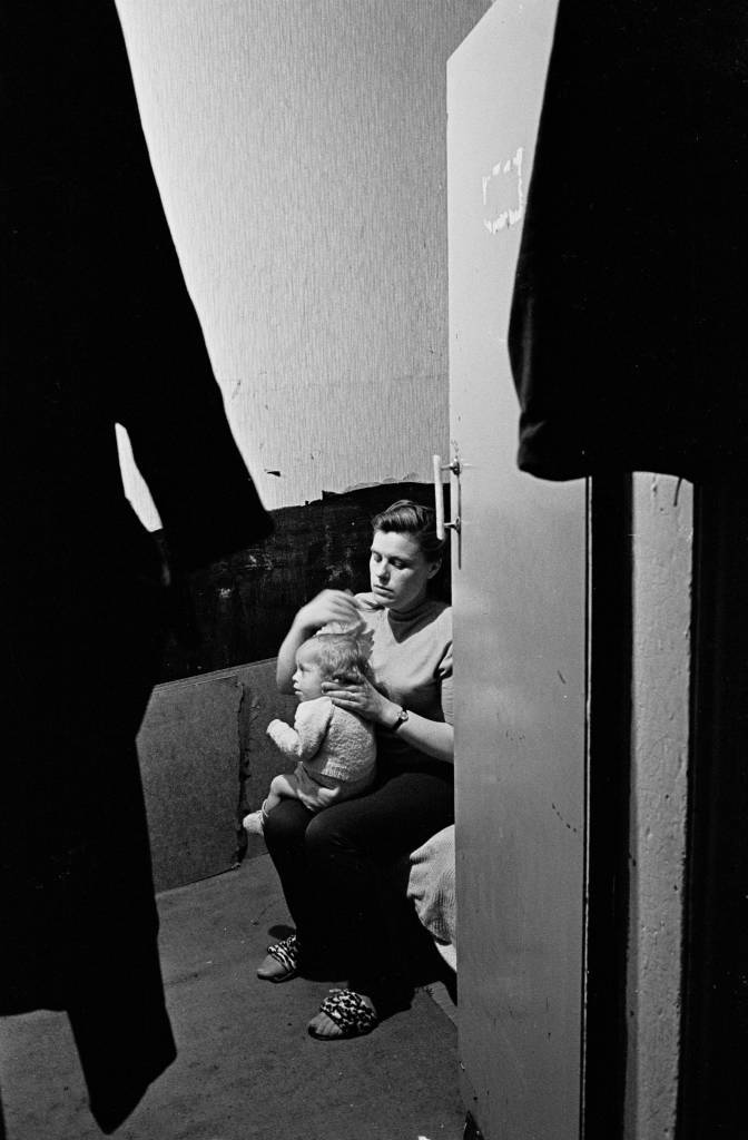 Peggy Rump brushing the hair of her baby, bedroom Rothschild dwellings 1969
