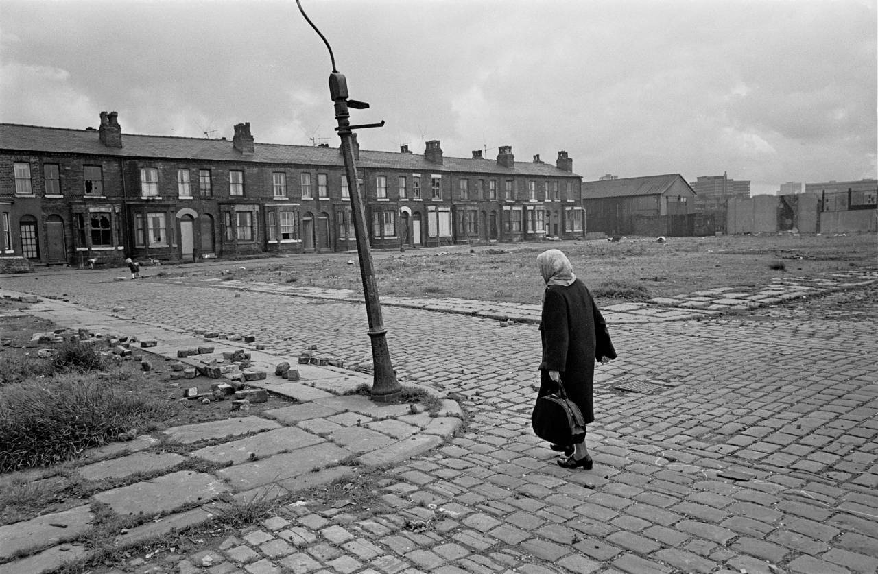 Pensioner crossing derelict land towards her home, Salford 1971