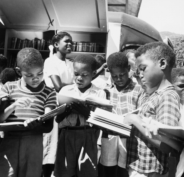 In the yard of a rural Trinidad School, young students browse through the books of a bookmobile belonging to the Government Central Library of Trinidad and Tobago, August 1956.