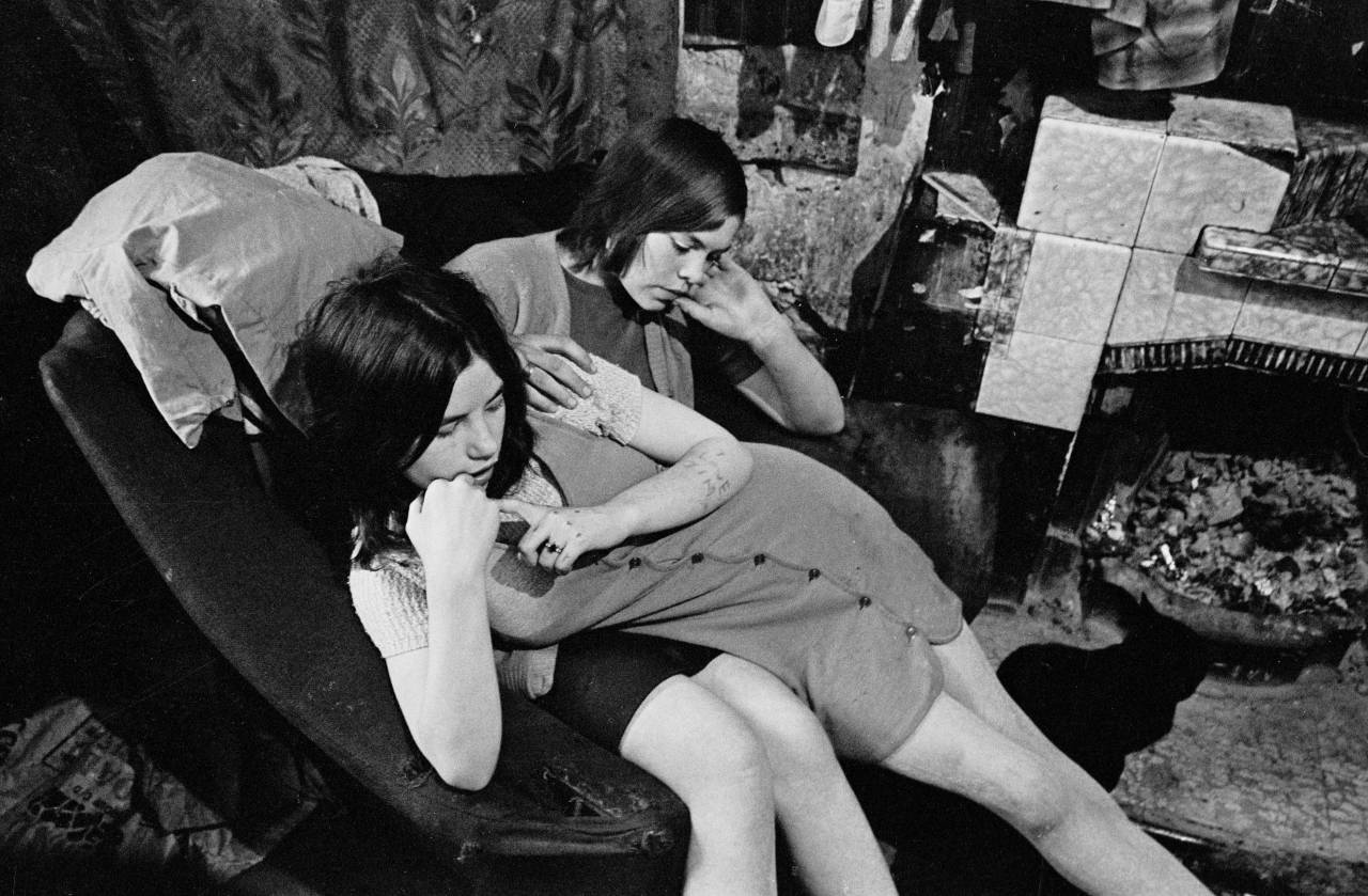 Sisters sharing a chair in a Gorbals slum tenement 1970