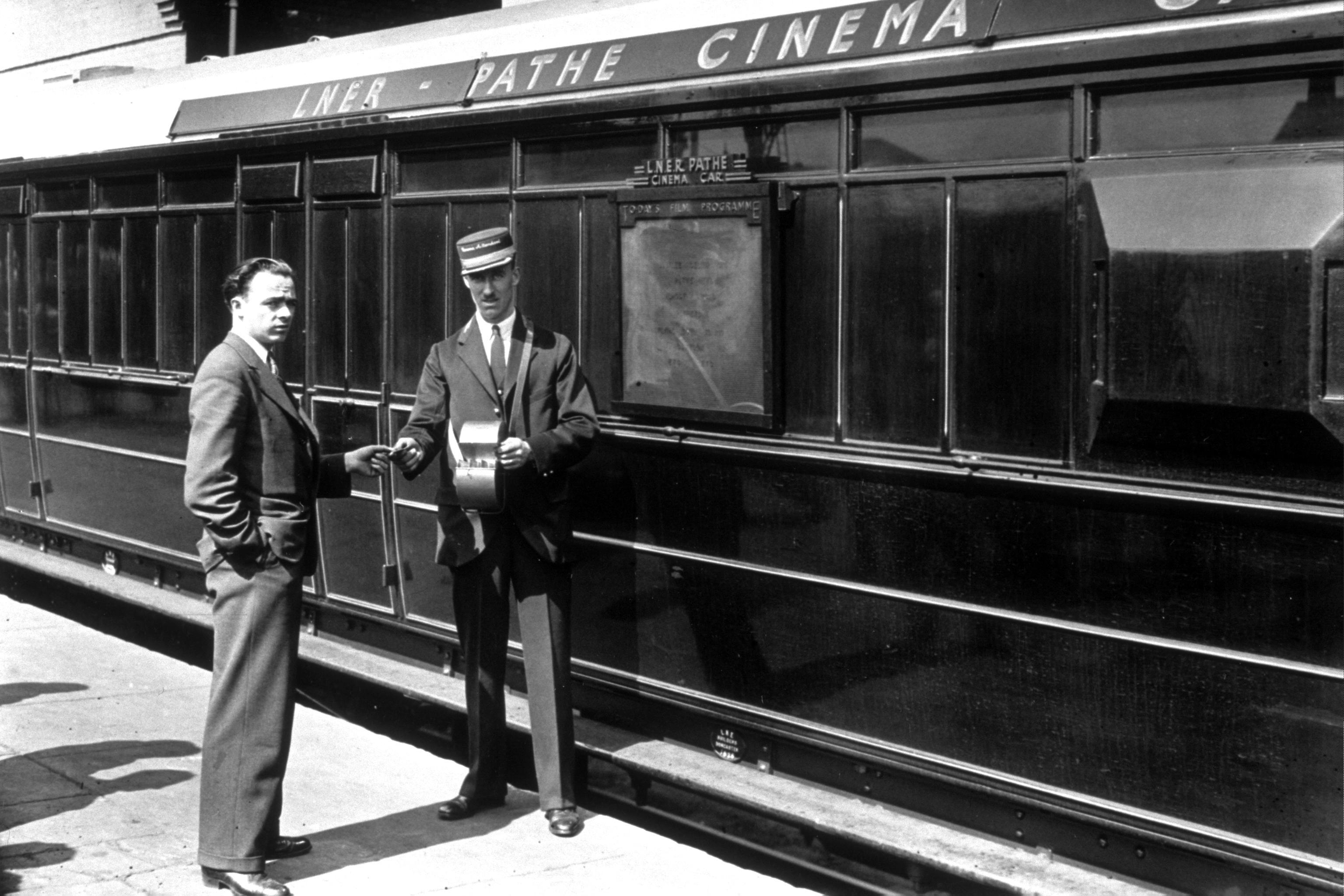 1938: A cinema attendant giving a ticket to a passenger for the Pathe cinema car, which ran on LNER trains. (Photo by Topical Press Agency/Getty Images)