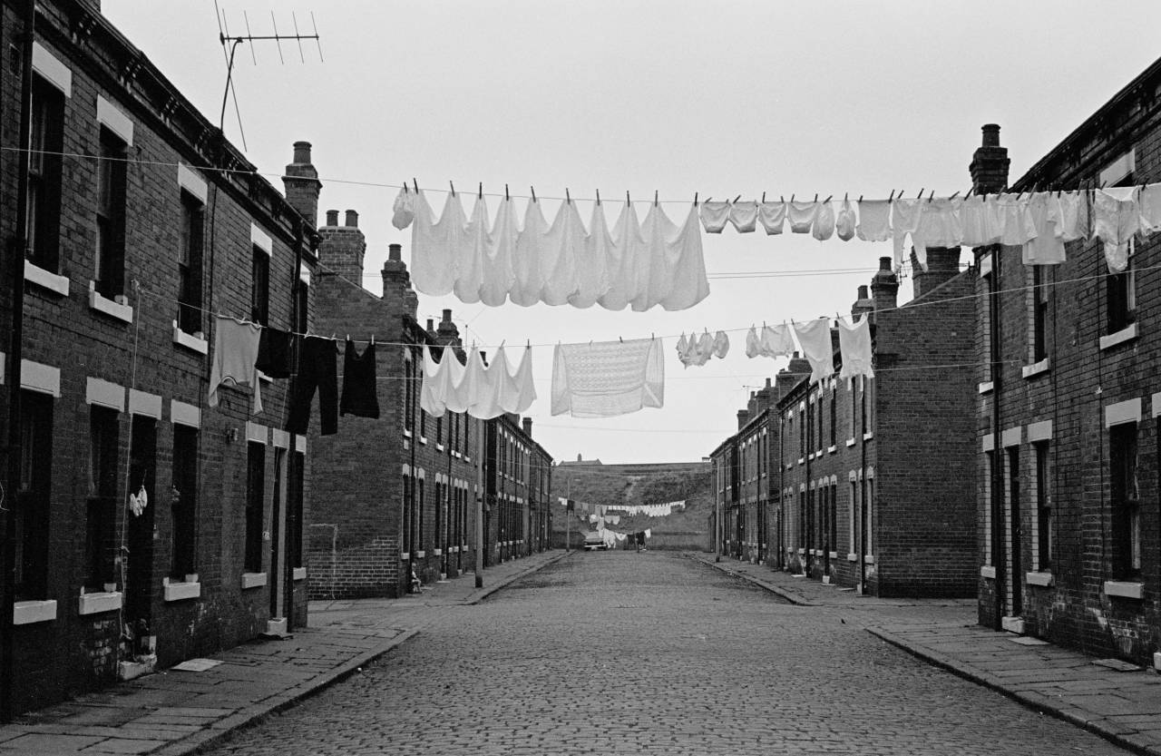 Washing hanging out to dry across back to back housing street, Leeds 1970