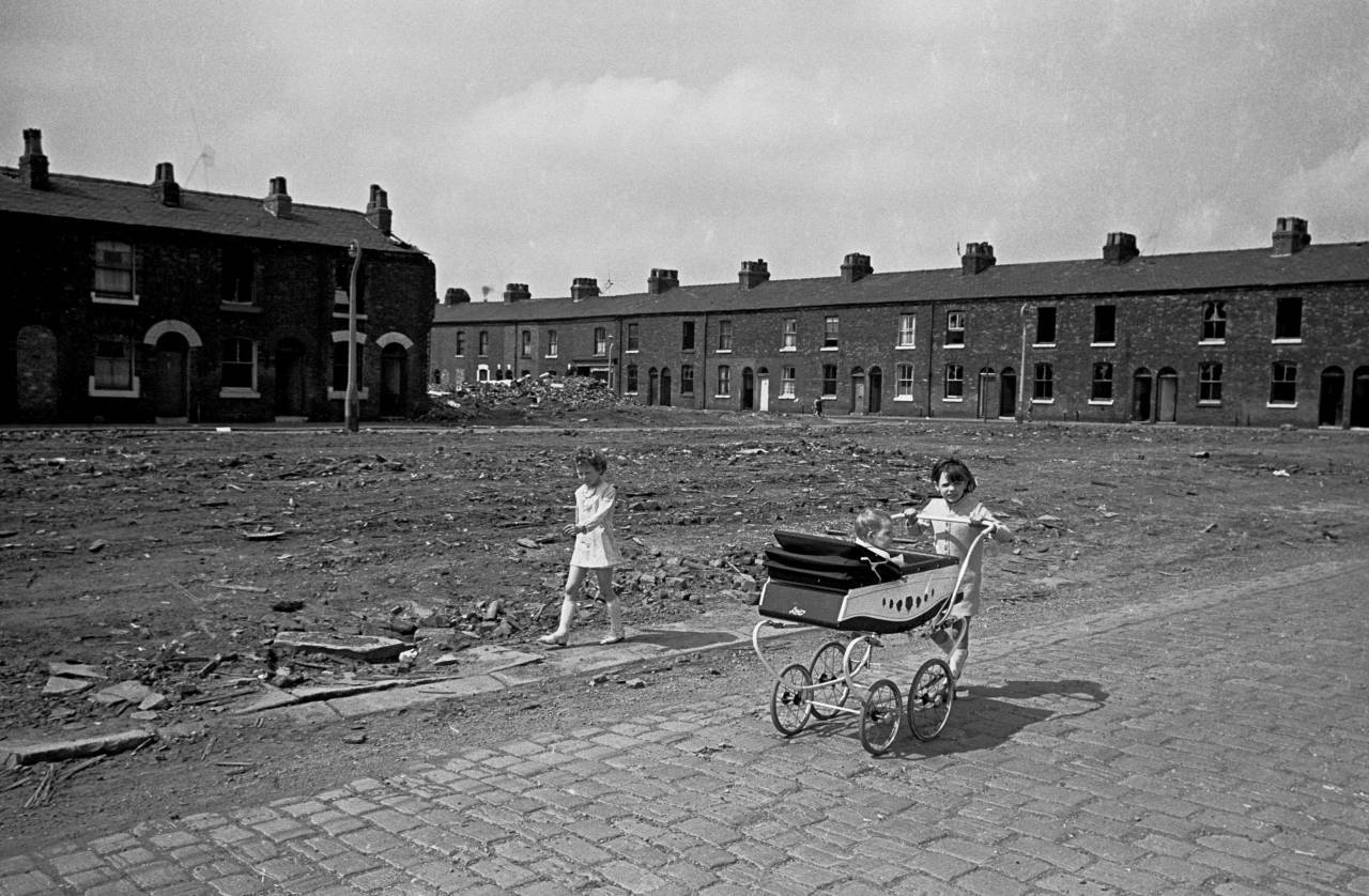 Young girls take baby sister for a walk, Salford 1969