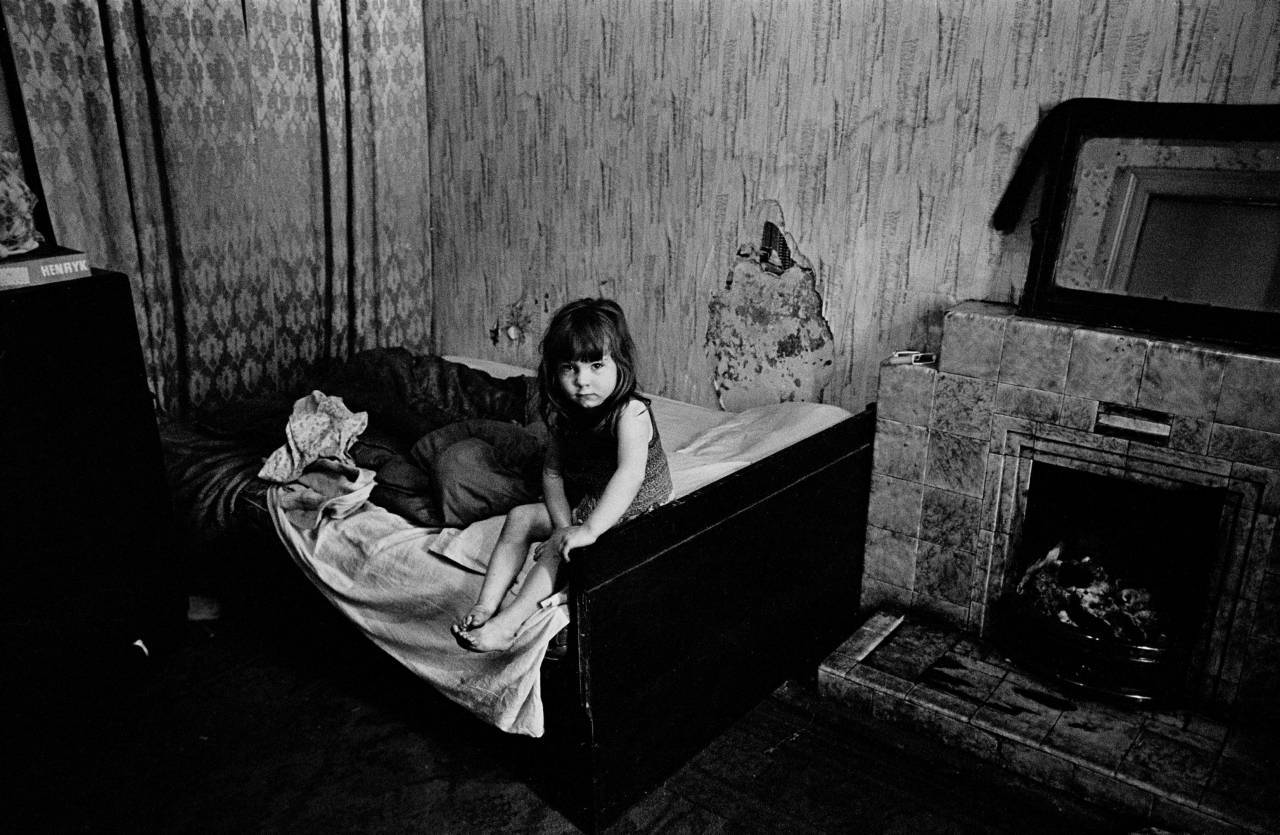 Child in damp semi derelict tenement flat Glasgow 1970