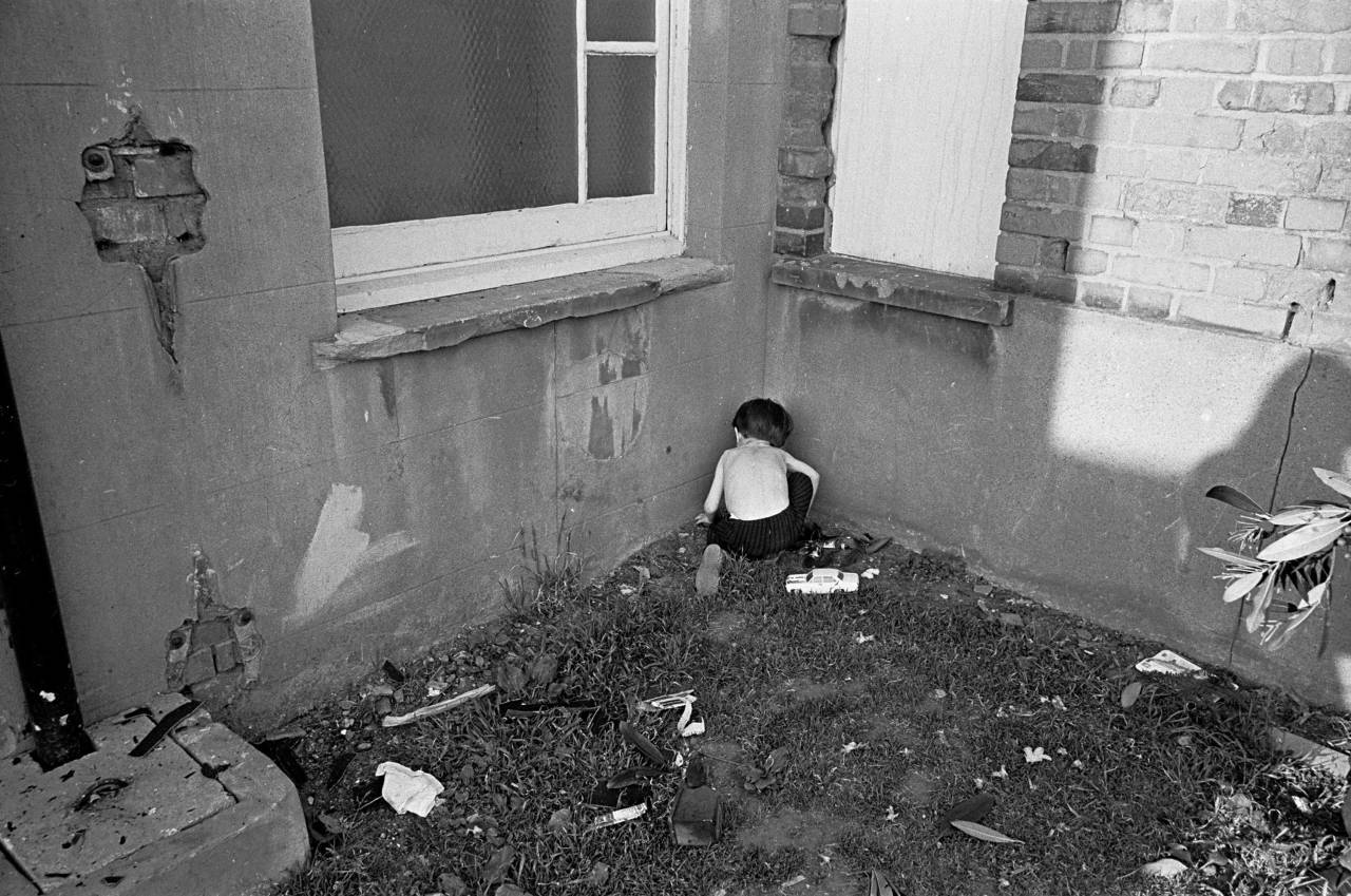 Child playing in the courtyard of a homeless hostel London 1969