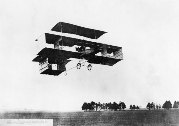 Henri Farman (1874-1958) flying his Voisin box-kite during a period when it was temporarily converted to a tri-plane. Henry Farman, the son of the Paris correspondent of the London Standard, took up flying after deciding it would be safer then racing motorcycles or cars. He became associated with the Voisin brothers, designers and builders of aeroplanes, and later became well known for his skill in handling the machines. On 13 January 1908, he made aviation history when he completed the first circular kilometer flight in Europe at Issy-les- Molineaux.