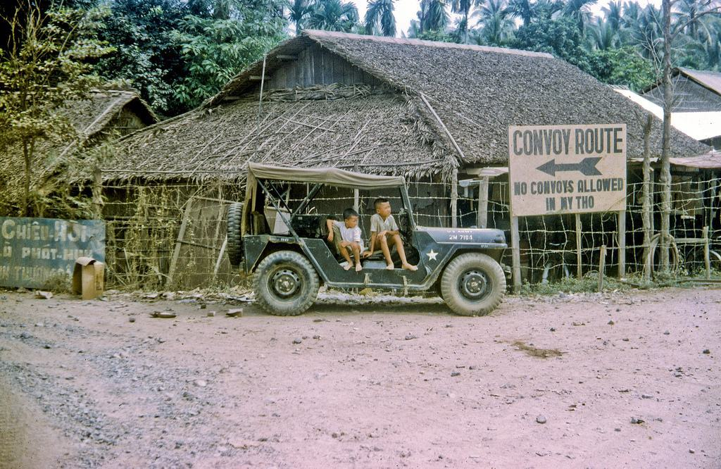 Road to My Tho in Nov 1968 Local kids sit in the jeep of the MP's who are directing traffic for a passing convoy. Along the road between Dong Tam and the city of My Tho in Dinh Tuong Province, Vietnam IV Corps, in 1968. (scanned colour slide)