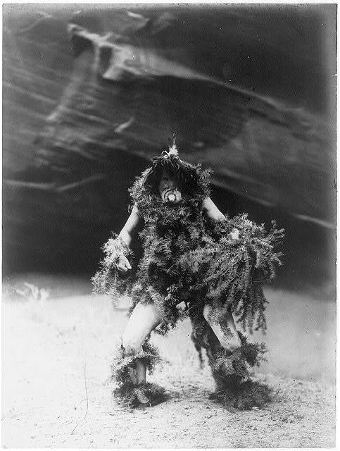 "Title: Tonenili--Navaho Creator(s): Curtis, Edward S., 1868-1952, photographer Date Created/Published: c1905 January 6. Medium: 1 photographic print. Summary: Navajo man bedecked in hemlock boughs and mask of a clown associated with the mischievous rain god Tonenili, ""Water Sprinkler""."