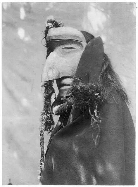 Title: Nuhlimahla--Qagyuhl Creator(s): Curtis, Edward S., 1868-1952, photographer Date Created/Published: c1914 November 13. Medium: 1 photographic print. Summary: Person wearing ceremonial mask of the Nuhlimahla during the during the Winter Dance ceremony. These characters impersonated fools and were noted for their devotion to filth and disorder.