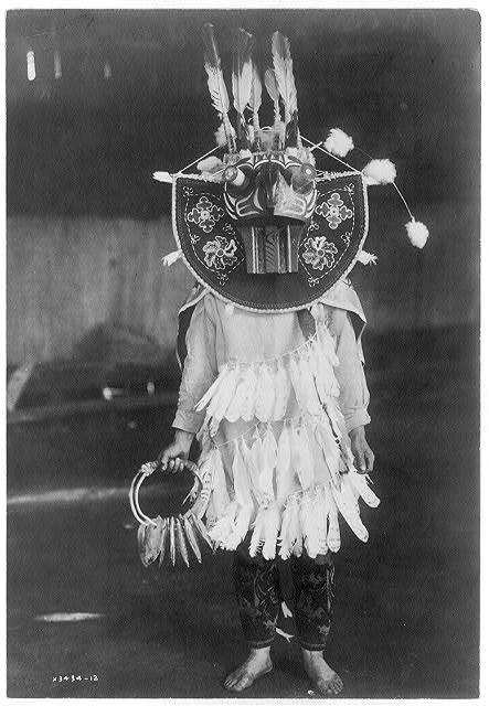 Title: Masked dancer--Cowichan Creator(s): Curtis, Edward S., 1868-1952, photographer Date Created/Published: c1913 June 16. Medium: 1 photographic print. Summary: Dancer wearing oversize mask, three rings of feathers in front of clothing, holding a rattle.