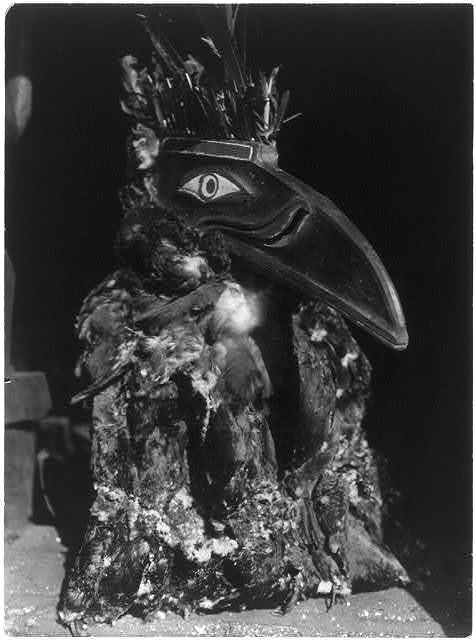 Title: Kwahwumhl--Koskimo Creator(s): Curtis, Edward S., 1868-1952, photographer Date Created/Published: c1914 November 13. Medium: 1 photographic print. Summary: Dancer wearing raven mask with coat of cormorant skins during the numhlin ceremony.