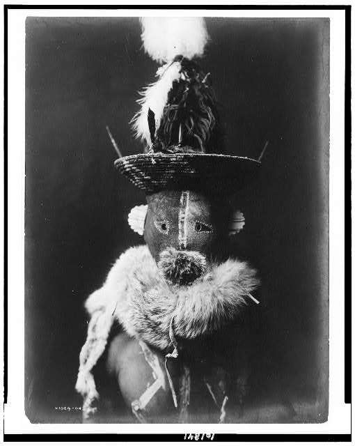 Title: [Zahadolzha--Navaho] Creator(s): Curtis, Edward S., 1868-1952, photographer Date Created/Published: 1904, c1905. Medium: 1 photographic print. Summary: Indian, head-and-shoulders portrait, facing front, wearing leather mask with basket cap, fur ruff, nude torso painted with white lines.