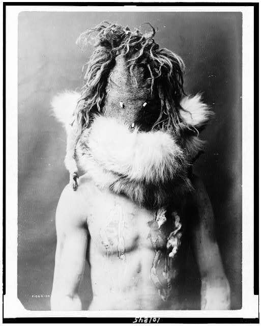 Title: [Nayenezgani--Navaho] Creator(s): Curtis, Edward S., 1868-1952, photographer Date Created/Published: 1904, c1905. Medium: 1 photographic print. Summary: Indian, half-length portrait, facing front, wearing dark mask, fur ruff, paint on torso.