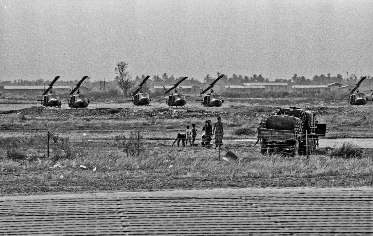 Airfield, Dong Tam, Dec 1968 A line of Bell UH-1 Huey's used by the 9th Infantry Division for air insertions in and around Dinh Tuong Province down in the Mekong Delta. I only took one serious ride on one these when I and an officer were taken in and dropped off near a remote hamlet. The ride at nearly 140 knots at very low altitude to avoid enemy fire was incredible. When I say low we literally had to gain altitude to clear the dikes in the rice paddies. I sat between and just behind the pilot and co-pilot for the whole trip taking it all in. When we got to the LZ it was too wet to land so we had to jump out of the chopper as it hovered. After that anything any amusement park has to offer cannot compete. I shot this series on one of my infrequent visits to Dong Tam with an old Practiflex 35mm camera I initially brought over. Said camera had been picked up a pawn shop in Fresno by my dad back in the late '50's.