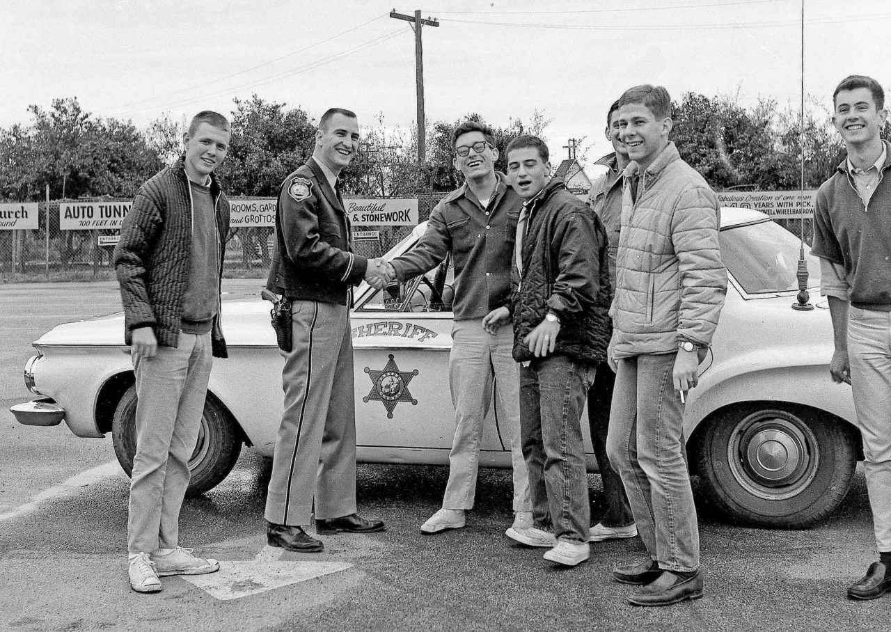 """Encounter with the Law -- 23 March 1963 While out horsing around on a overcast Fresno morning the Fresno County Sheriff's units stopped to check out our """"suspicious"""" activities. All ended peacefully when they learned we were just a bunch of harmless college boys. Future sports writer Doug Krikorian seen shaking the Deputy's hand"""