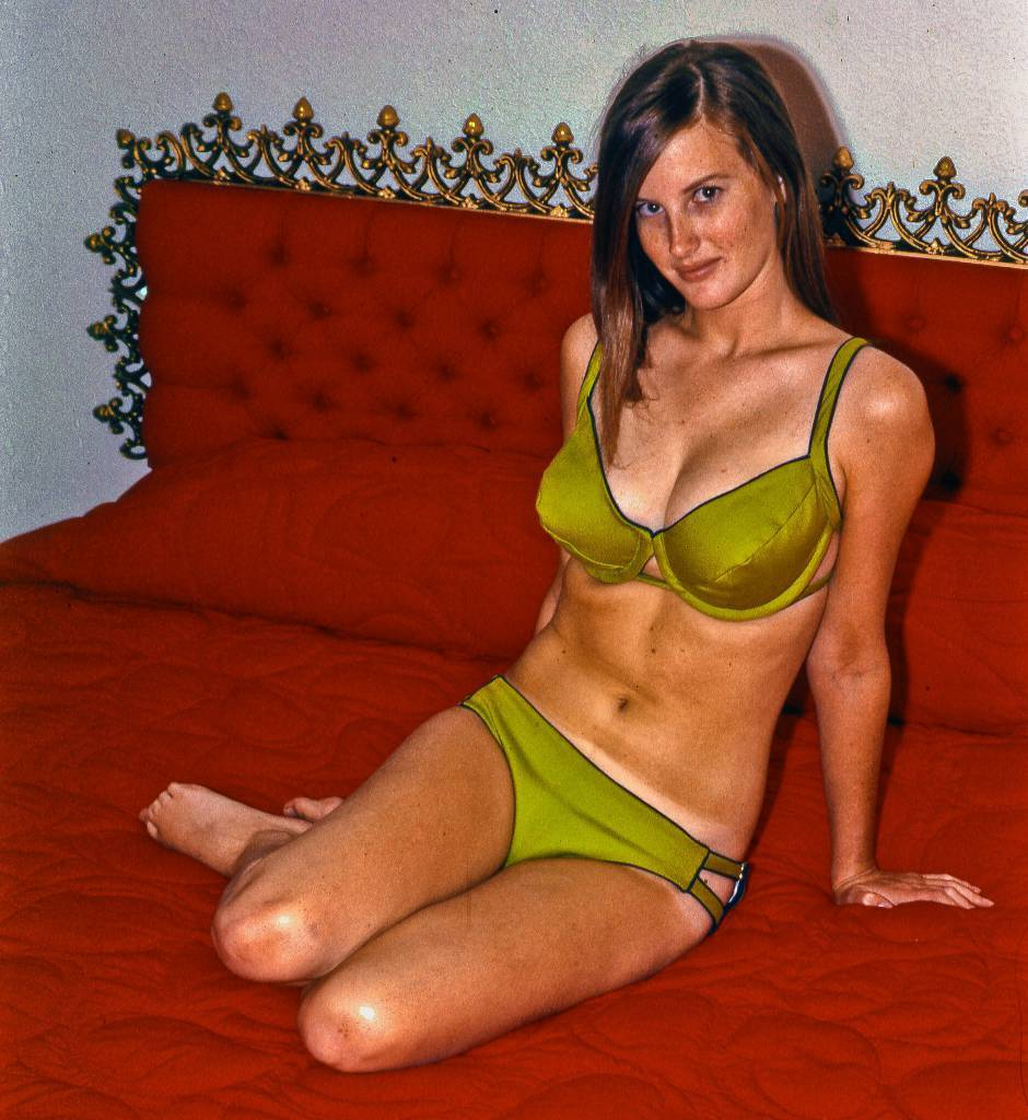 College girlfriend in July of 1967 She made the bathing suit herself as she did most of her clothes. She posed for me on this colorful bed at a friend's house. For some reason her beautiful red hair came out looking dark brown in this color slide.We started dating in early 1965 and spent 5 good years together.