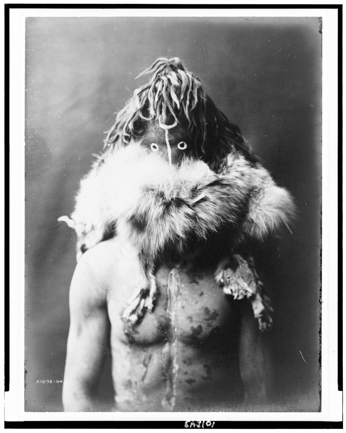 Title [Nayenezgani--Navaho] Summary Indian, half-length portrait, facing front, wearing dark mask, fur ruff, paint on torso. Contributor Names Curtis, Edward S., 1868-1952, photographer Created / Published 1904, c1905.