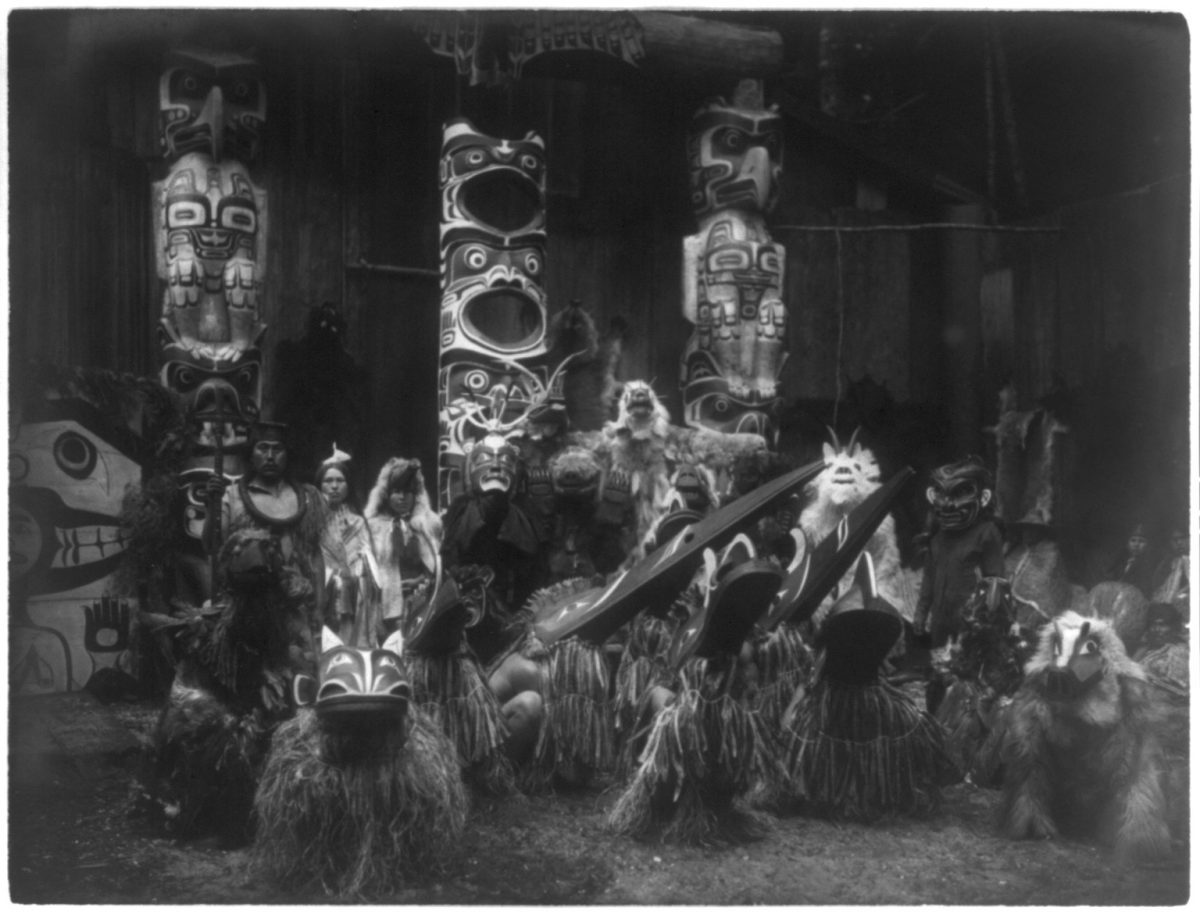 Title Masked dancers--Qagyuhl Summary During the winter ceremony, Kwakiutl dancers wearing masks and costumes, crouch in foreground with others behind them. The chief on the far left holds a speaker's staff. Three totem poles in background. Contributor Names Curtis, Edward S., 1868-1952, photographer Created / Published c1914 November 13.
