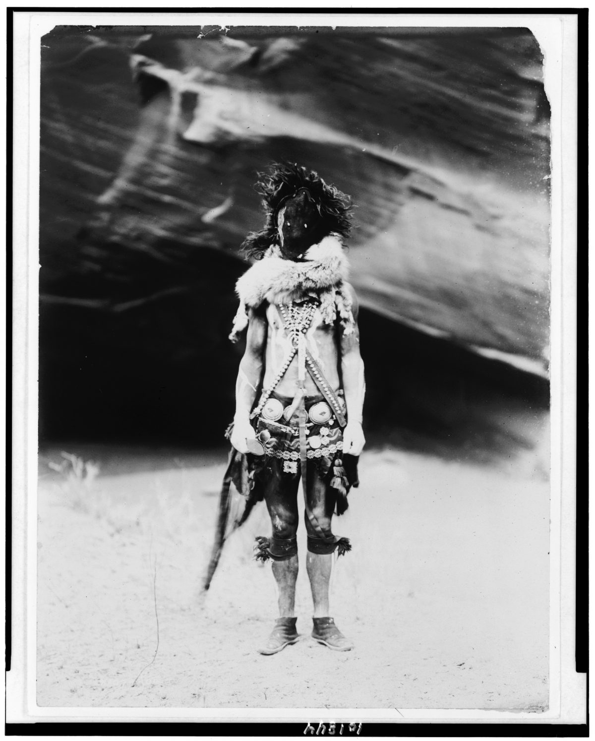 Title [Nayenezgani--Navaho] Summary Indian, full-length portrait, standing, facing front, wearing dark leather mask, fur ruff, cloth girdle, silver concho belt and necklaces. Contributor Names Curtis, Edward S., 1868-1952, photographer Created / Published 1904, c1905.