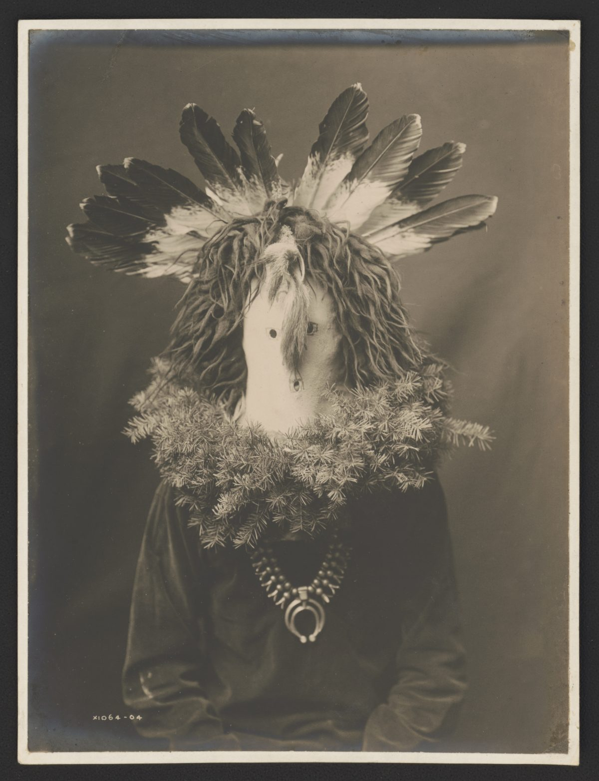Title Haschogan (House God) - The Yebichai Hunchback Summary Photograph shows a Navajo man, half-length, seated, facing front, wearing a ceremonial mask with feathers and with fir or spruce branches forming a wreath around the shoulders. Contributor Names Curtis, Edward S., 1868-1952, photographer Created / Published [1904]