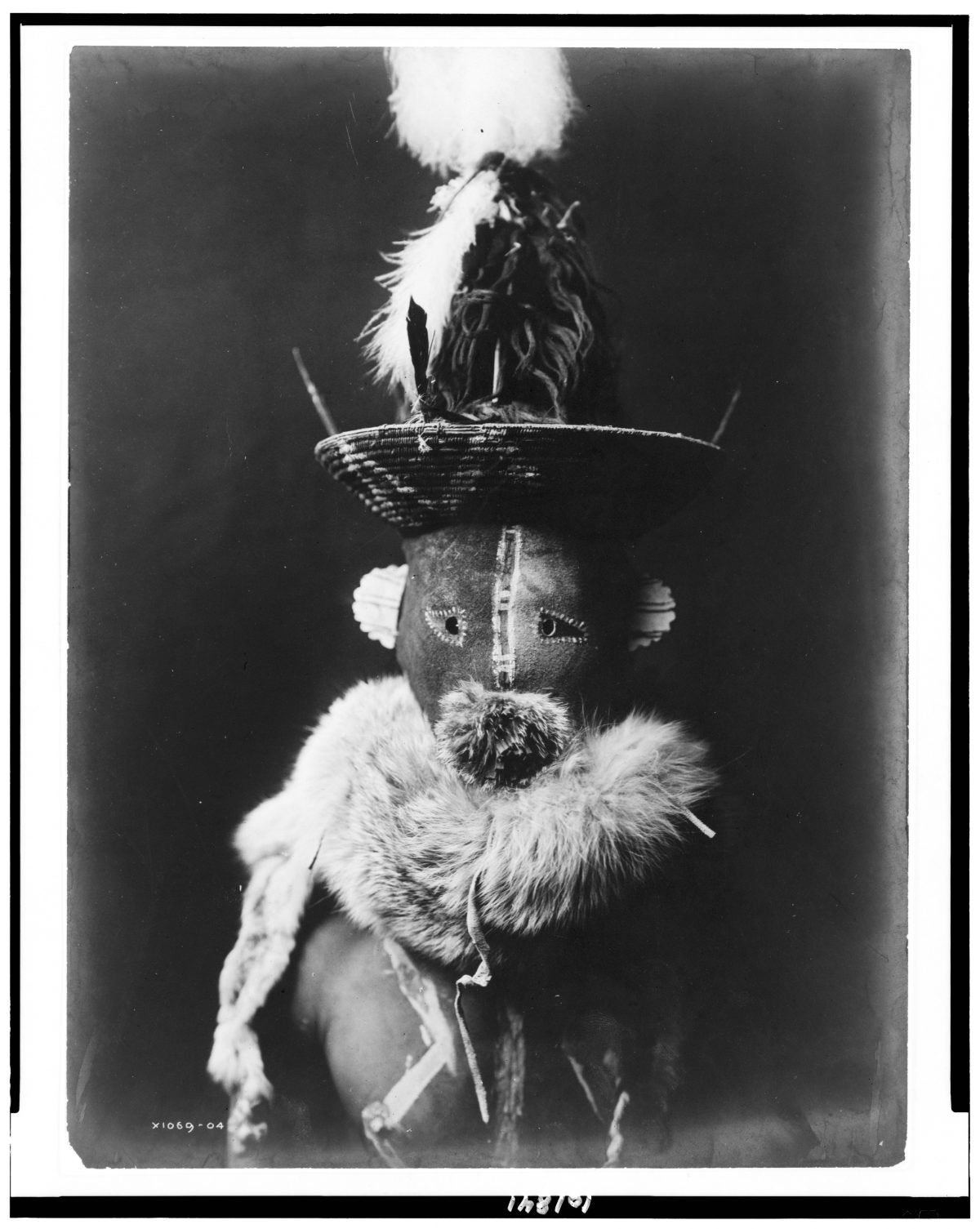 Title [Zahadolzha--Navaho] Summary Indian, head-and-shoulders portrait, facing front, wearing leather mask with basket cap, fur ruff, nude torso painted with white lines. Contributor Names Curtis, Edward S., 1868-1952, photographer Created / Published 1904, c1905.