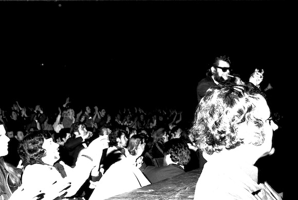 """Sunglasses Ron"" Fahey, top right, leads the applause onstage at the Rainbow, Finsbury Park, London, spring 1977. Photo: Neal Purvis"