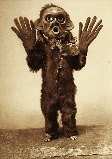 "Title: Hami--Koskimo Creator(s): Curtis, Edward S., 1868-1952, photographer Date Created/Published: c1914 November 13. Medium: 1 photographic print. Summary: Koskimo person wearing full-body fur garment, oversized gloves and mask of Hami (""dangerous thing"") during the numhlim ceremony."