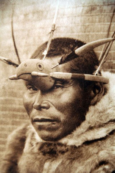 An Edward Curtis photograph from 1928, showing an Inuit hunter/fisherman wearing a bird mask.