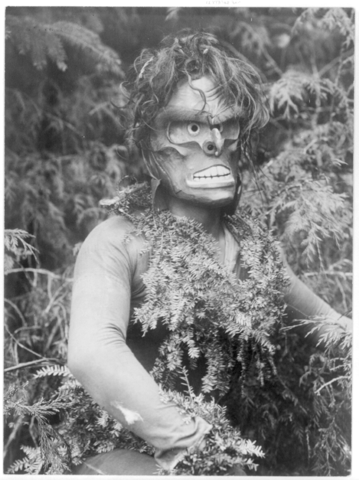 "Title Paqusilahl--Qagyuhl Summary Dancer representing Paqusilahl (""man of the ground embodiment""), wearing a mask and shirt covered with hemlock boughs, representing paqus, a wild man of the woods. Contributor Names Curtis, Edward S., 1868-1952, photographer Created / Published c1914 November 13."