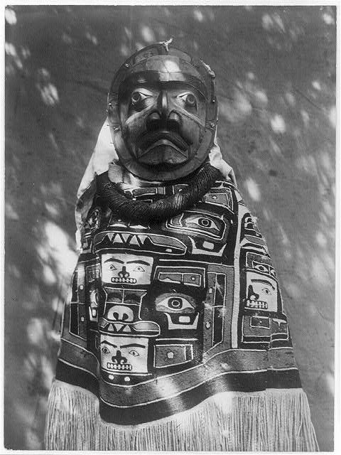 Edward C. Curtis from the Library of Congress. CEREMONIAL DRESS OF THE KWAKIUTL AND NOOTKA TRIBES OF BRITISH COLUMBIA, 1914. Woman wearing a fringed Chilkat blanket, a hamatsa neckring and mask representing deceased relative who had been a shaman 3y
