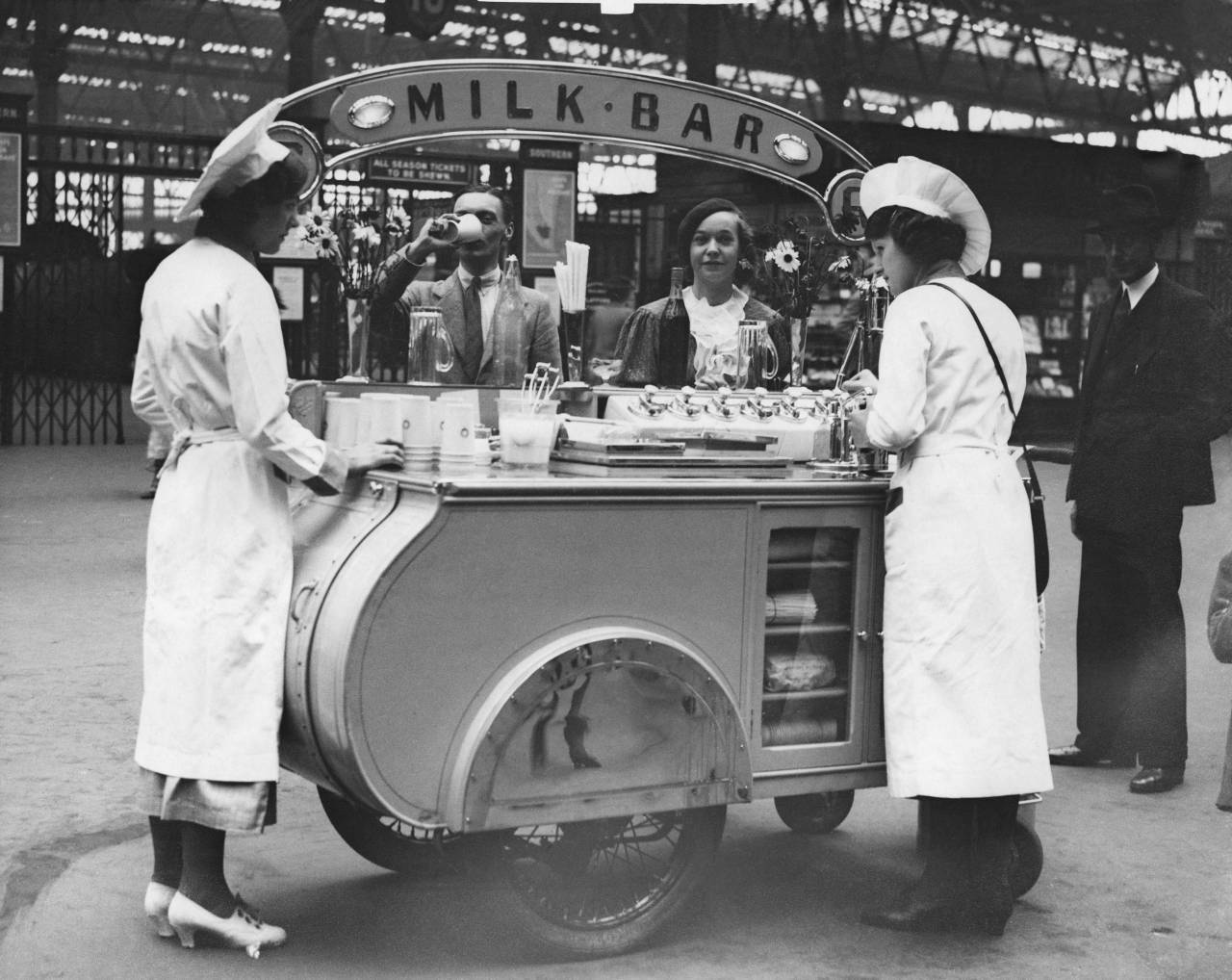 1st June 1937: Customers drinking at the portable milk bar which travels the platforms at Waterloo Railway Station. It is the first of its kind on any station in Great Britain. (Photo by Fox Photos/Getty Images)