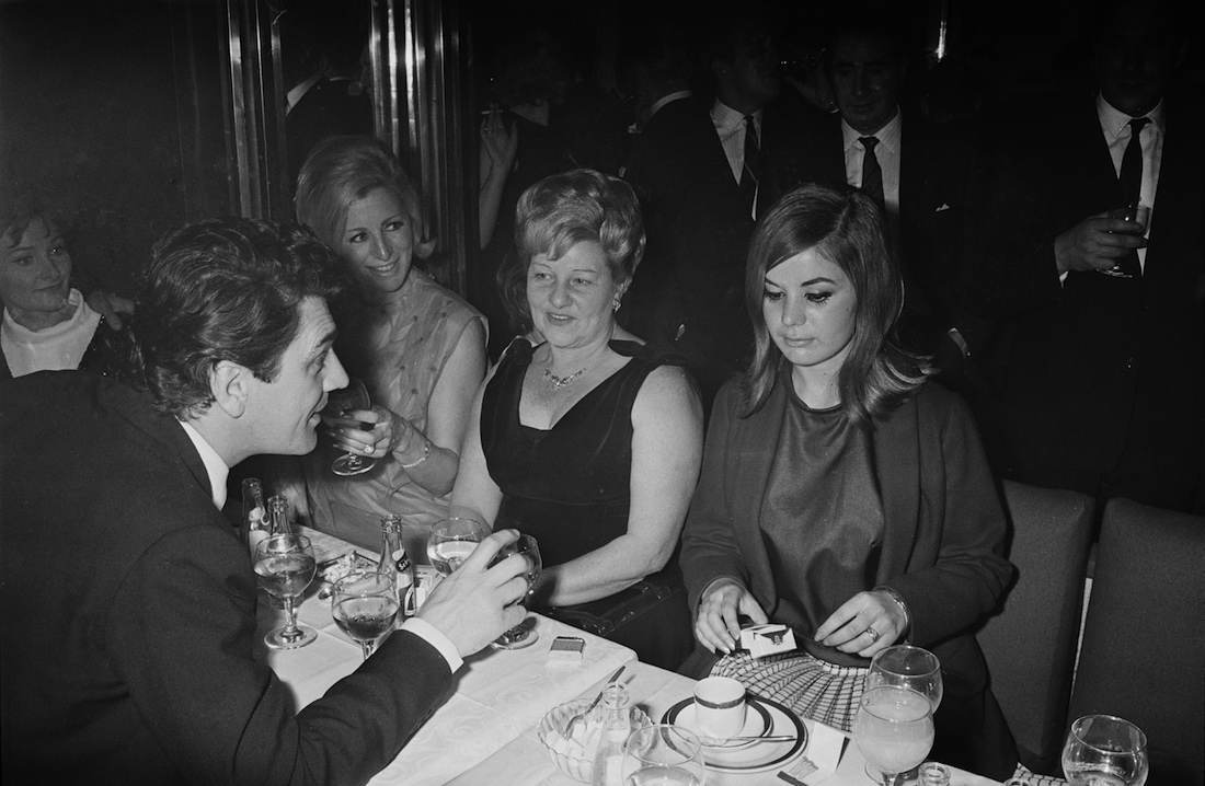 British actor Edmund Purdom (1924 - 2009, left) with Frances Shea (1943 - 1967, right), wife of English gangster Reggie Kray, at the El Morocco, a nightclub owned by the Kray Twins, in Soho, London, 30th April 1965. The Kray twins' mother, Violet Kray, is at centre (in dark dress), sitting to her right is Dolly Kray, wife of Charlie. Actress Adrienne Corri is at far left. (Photo by Larry Ellis/Daily Express/Hulton Archive/Getty Images)