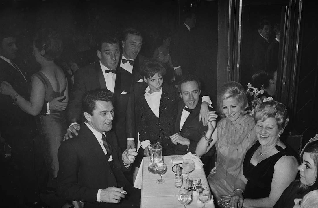 Frances Shea (1943 - 1967, far right) with her husband, English gangster Reggie Kray (1933 - 2000, standing, third from left) and celebrity guests at the El Morocco, a nightclub owned by the Kray Twins, in Soho, London, 30th April 1965. Kray has his hand on the shoulder of British actor Edmund Purdom (1924 - 2009). Behind Reggie can be seen his brother Charlie (1926 - 2000). At centre is Actress Adrienne Corri with her arm around Welsh actor Victor Spinetti (1929 - 2012). On his left can be seen Charlie's wife Dolly who in turn sits next to the twins' mother, Violet Kray. (Photo by Larry Ellis/Daily Express/Hulton Archive/Getty Images)