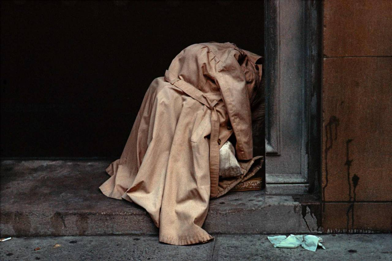 1984, New York, homeless person under raincoat