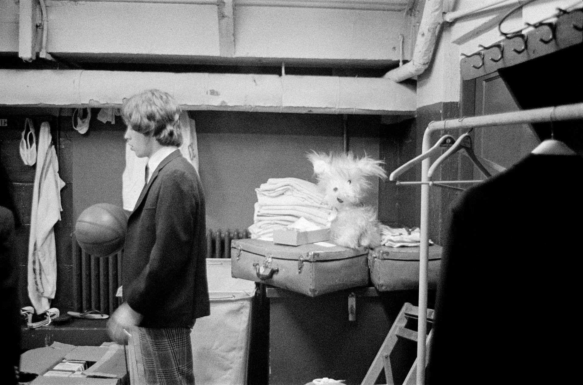 Mick backstage at the Boston Garden (1965) 'This photo of Mick with a basketball was taken at the stadium home of the Boston Celtics team, who were topping the league at the time. Their discarded clothes and jockstraps littered the room, which also played host to various cuddly toys left by the local fan club'